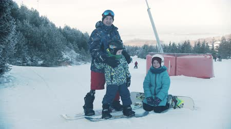 スノーボード : 14-12-19 RUSSIA, KAZAN: Family snowboarding - A man with prosthetic leg teaching his kids how to get on the snowboard 動画素材