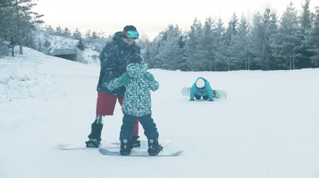 prosthesis : 14-12-19 RUSSIA, KAZAN: Family snowboarding - A man with prosthetic leg watching his kids trying to do a basic small jumping trick with the snowboard Stock Footage