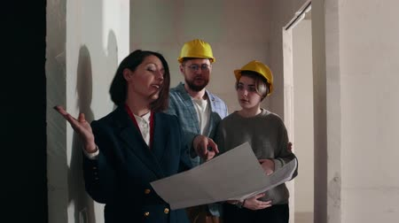 mülkiyet : A young woman real estate agent showing apartment to a young family - showing all the rooms by the scheme - all the people wearing helmets