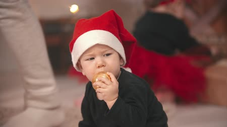 праздник : Christmas concept - a little baby boy putting a christmas ball in his mouth Стоковые видеозаписи