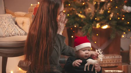 deer : Christmas concept - A young woman playing with her little baby in christmas studio - a baby holding toy deer