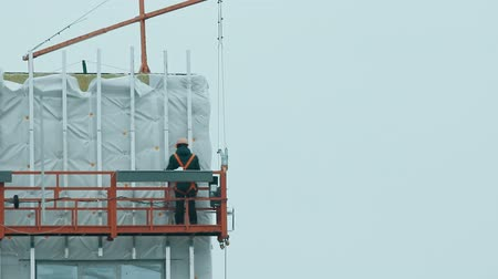 csatolt : A man worker lifting up to the top of the building for continue constructing