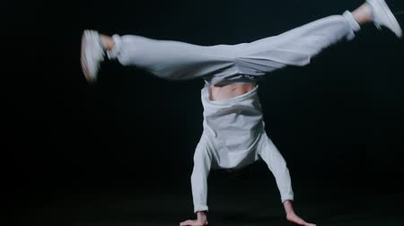 hiphop : Young man dancer performing break dance trick in the dark studio