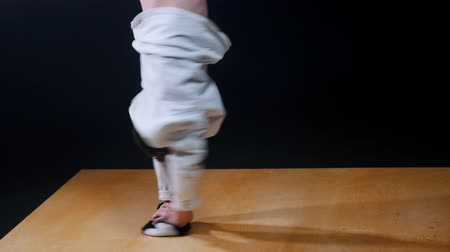keep fit : Young fit man break dancer in white clothes spinning aroung on one hand and keeping the balance Stock Footage