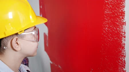 painting home : Un niño pequeño que pinta la pared clara con pintura roja Archivo de Video