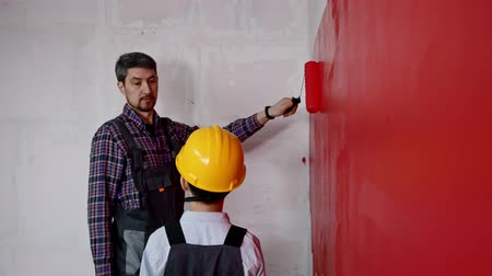 decorating : A man painting walls and gives his son the roller Stock Footage