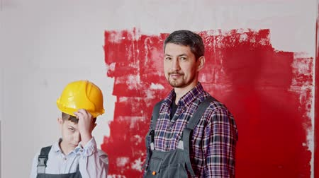 rolki : Smiling little boy and his father painting walls - pulls out their rollers and the boy puts on helmet