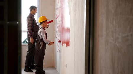 decorating : Repairing draft apartment - little boy and his father drawing lines on the wall with red paint