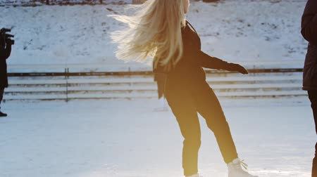 paten yapma : A young blonde woman skating on the ice rink Stok Video