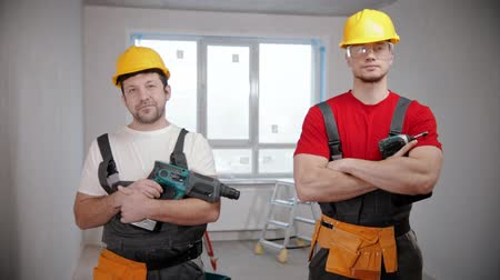 renovação : Two men workers standing in draft apartment holding their instruments