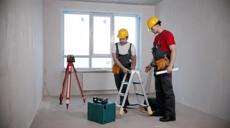 skillful : Apartment repair - two men workers looking around in the draft room and start to making a plan