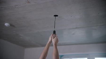 электрический : Mans hands unscrews a light bulb under the ceiling