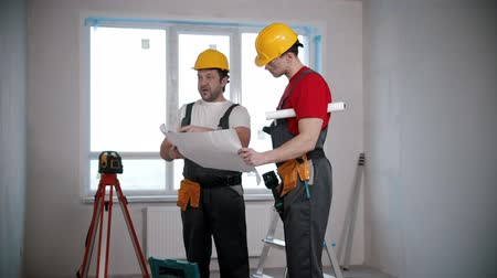 maintenance : Apartment repair - two men workers discussing an apartment plan before working on it Stock Footage