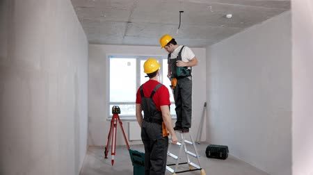 kask : Apartment repair in the room - one man worker passes drill to another Stok Video