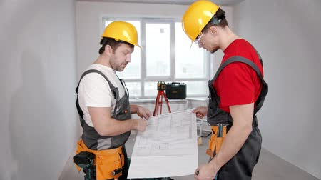 skillful : Apartment repair - two men workers discussing the apartment plan Stock Footage