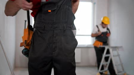 ドラフト : A young man worker putting on a working belt