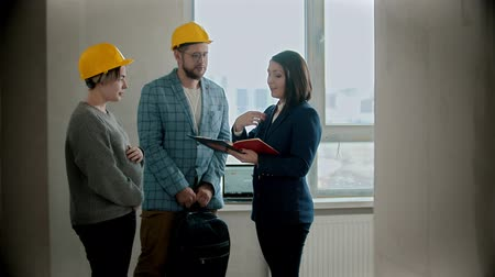 consulting : A pregnant woman with her husband talking with a real estate agent in draft apartment Stock Footage