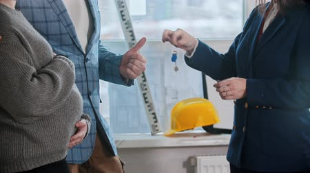 аренда : A real estate agent gives the keys to apartment to a young family and man showing a thumb up