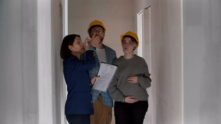 mülkiyet : A real estate agent showing a new draft apartment to a family and pointing at the ceiling Stok Video