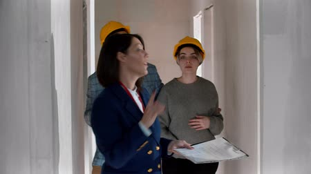 консультация : A real estate agent showing a new draft apartment to a young married couple in helmets - looking around Стоковые видеозаписи