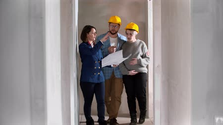 mülkiyet : A real estate agent showing a new draft apartment to a young married couple in yellow helmets holding a layout on the paper Stok Video
