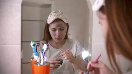 escova de dentes : A young woman applying a face mask on her face using a brush Stock Footage