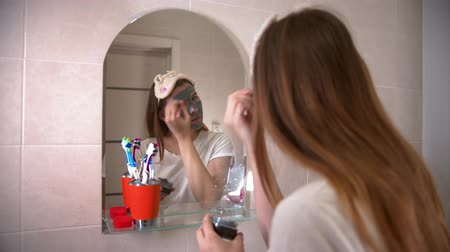 escova de dentes : A young woman applying a grey face mask on her face using a brush