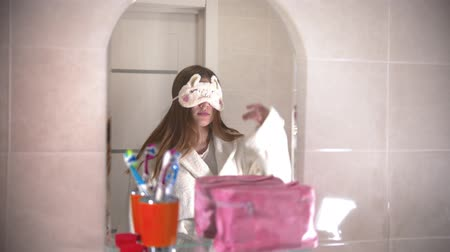 escova de dentes : A young woman takes off her sleeping mask and look at herself in the mirror