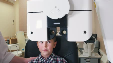 slit : Ophthalmologist treatment - a little boy checking eyes with big device
