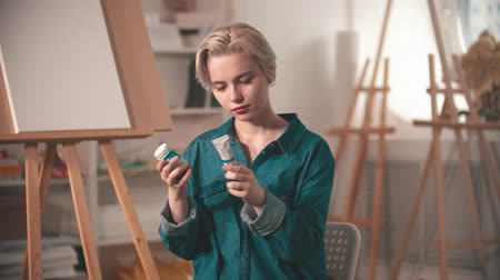 галерея : A young woman artist looking at two different tubes of a blue paint