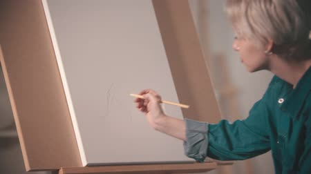 мольберт : A young woman artist making sketch on the canvas using a pencil Стоковые видеозаписи