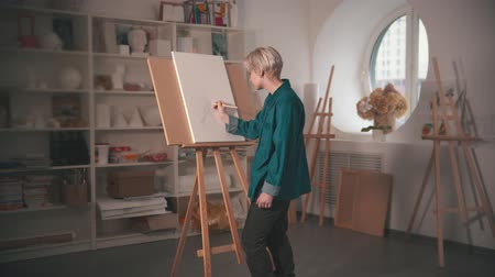 холст : A young blonde woman artist drawing sketch on the canvas and looking at it