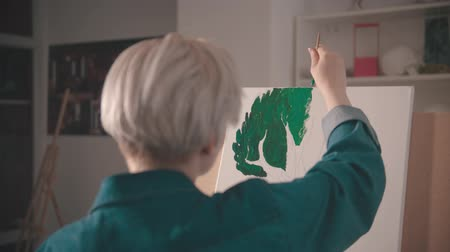 galerie : A young woman with short hair painting upper branches of tree in green color in the art studio Stockvideo