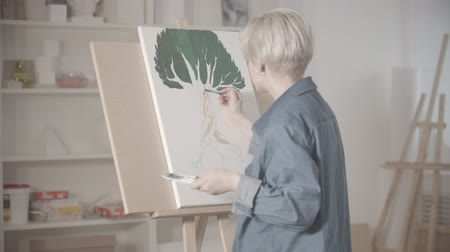 холст : A young blonde woman draws a tree with paints Стоковые видеозаписи