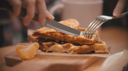 twarożek : A woman cutting a waffle covered in syrup in the plate Wideo