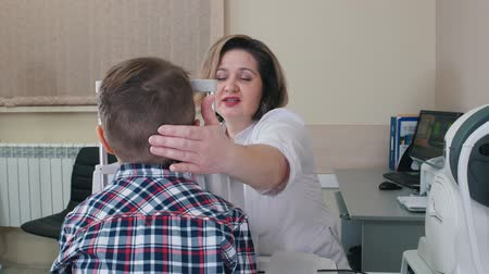 yarık : Ophthalmologist treatment - mature smiling woman checking boys eyes using big special device in the clinic Stok Video