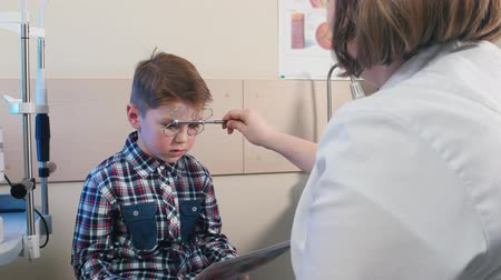yarık : Ophthalmologist treatment - woman doctor about to check the eyes of a little boy Stok Video