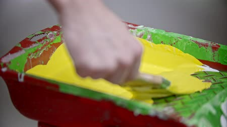 splattered : A person drowns the brush in yellow paint in the paint tray