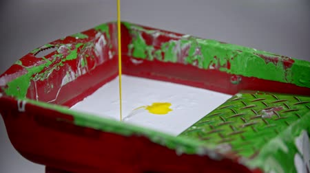 dekoratör : A person pouring yellow paint in the paint tray with white paint