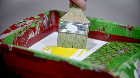 splattered : A person mixing white and yellow colors in the paint tray using a brush Stock Footage