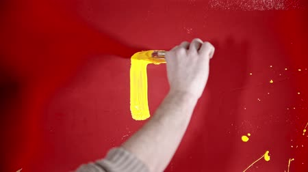 dekoratör : A person painting with a yellow paint on the red wall Stok Video