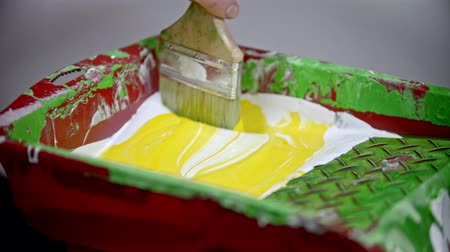 splattered : Mixing white and yellow colors in the paint tray using a synthetic brush