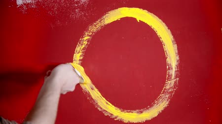 splattered : A person painting a smiling face with a yellow paint on the red wall
