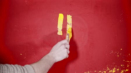 splattered : A person painting a smiley face with a bright yellow paint on the red wall