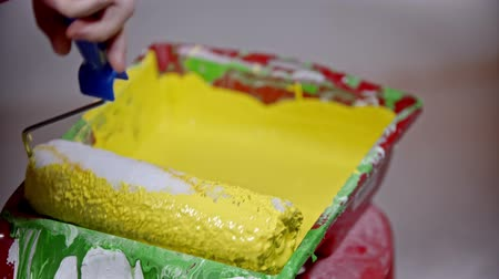 splattered : An apartment repair - person covering a roller in yellow paint in the paint tray