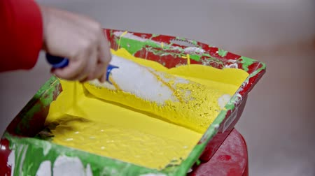 splattered : An apartment repair - person covering a roller in bright yellow paint in the paint tray