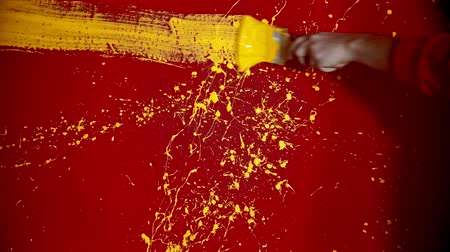 splattered : A man walking by the red wall and drawing a line with a yellow color using a brush Stock Footage