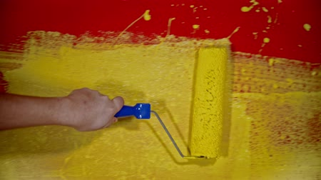 splattered : An apartment repair - a person painting a red wall with yellow paint using a roller Stock Footage