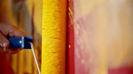 splattered : Painting a red wall with yellow paint using a roller Stock Footage