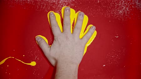 splattered : Putting a hand imprint with a bright yellow color on the red wall